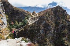 Traccia di montagna diritta di viaggiatore con zaino e sacco a pelo della donna vicino allo stupa buddista Fotografia Stock Libera da Diritti