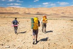 Traccia di pietra di camminata del deserto di tre viaggiatori con zaino e sacco a pelo Fotografia Stock