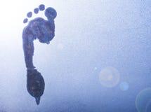 Traccia di un piede nudo su vetro congelato fotografia stock