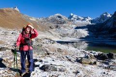 Traccia diritta della neve della montagna della donna di viaggiatore con zaino e sacco a pelo Fotografia Stock Libera da Diritti