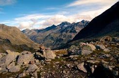Traccia rocciosa che conduce alla valle circondata dalle alte montagne in alpi svizzere Fotografia Stock