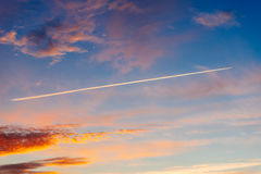 Trace of aircraft in the dramatic sky on sunset Stock Photo