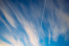 Trace of aircraft in morning sky with clouds Stock Photo