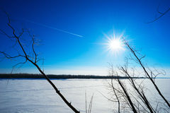 Trace of an airplane against a blue Sunny winter sky over the river. Stock Photo