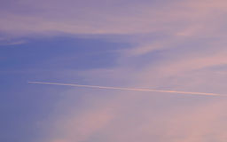 Trace of an airplane against the evening sky. Background blue sky with pink clouds at sunset Royalty Free Stock Images