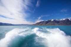 Trace of the boat. Picture trace of water from the powerful motor boats on the background blue sky and mountains with snow on top stock photos