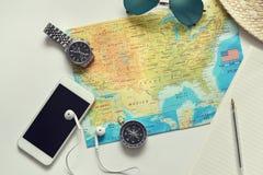 Trace con el teléfono, el compás, las gafas de sol y otros artículos en fondo llano Imagenes de archivo