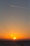 Trace d'avion au coucher du soleil. Photographie stock