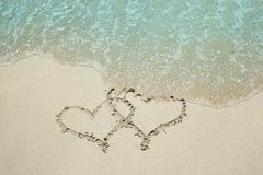 Trace de coeur dans le bord de la mer de sable Photos libres de droits