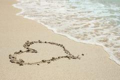 Trace de coeur dans le bord de la mer de sable Photo stock