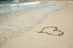 Trace de coeur dans le bord de la mer de sable Photos stock