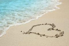 Trace de coeur dans le bord de la mer de sable Image libre de droits