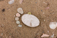 Trace feet made of a pebble stone close up on the sea sand deser Stock Photos