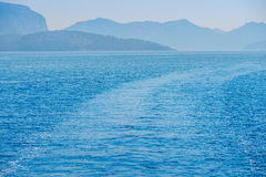 Trace of the ship on the blue water Royalty Free Stock Photography