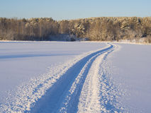 Trace of a snowmobile. Crossing a snow-covered lake under the ice cover Royalty Free Stock Photos
