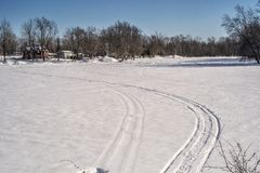Trace of snowmobile on a river. Snowmobile trace in a vast spaces on the frozen Rivière des Mille Îles in Ste-Rose, Laval, Quebec, Canada stock image