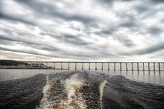 Trace of speed boat on blue sea water in manaus, brazil. Seascape with bridge on horizon on cloudy sky. travelling and vacation. a royalty free stock images