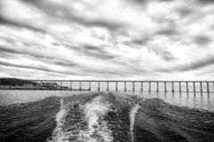 Trace of speed boat on blue sea water in manaus, brazil. Seascape with bridge on horizon on cloudy sky. travelling and royalty free stock photo