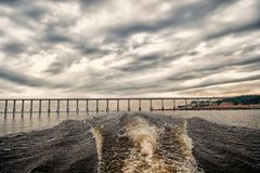 Trace of speed boat on blue sea water in manaus, brazil. Seascape with bridge on horizon on cloudy sky. travelling and stock images