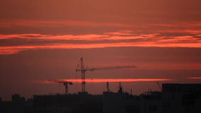 Trace on twilight sky speedy. Construction cranes in building site at backdrop airplane trace luminosity in sunlight at twilight sky east side stock video