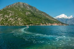 Trace on the water on a motorboat, in the background a small town Perast, Bay of Kotor Boka Kotorska, Montenegro. View from the. Small town Perast, Kotor Bay royalty free stock photo