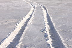 Trace of wheels on winter road. Close-up Stock Images