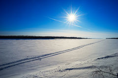 Traces of an airplane in the blue sky and from all-terrain vehicle on  frozen river . Stock Photo