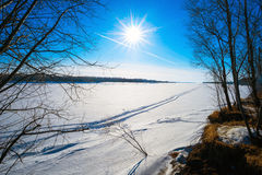 Traces of an airplane in the blue sky and from all-terrain vehicle on  frozen river . Royalty Free Stock Image