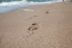 Traces of bare feet on wet sea sand Stock Photo