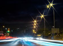 Traces of car lights on the evening street. Starburst of city lights. wide road leads to living area in the distance. busy night life concept royalty free stock photos