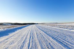 Traces of the car on snow. Snow-covered road, on which there were traces of the car to drive. Photo closeup, deep ruts on a background of blue sky on a sunny day Royalty Free Stock Images