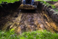 Traces of excavator tires digging pit in grassy soil during earth works stock photography