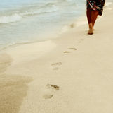 Traces of female legs on sand Stock Image