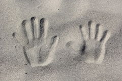 Traces of hands on the sand Stock Photo