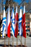 Flags of Poland and Israel. Israeli and Polish flags next to the Warsaw Ghetto Heroes Monument. The monument commemorates Jewish fighters who died during the Stock Image