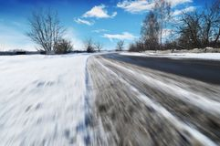 Free Traces Of A Car Tires On The Road In Motion Covered In White Snow Against Blue Sky With Clouds Royalty Free Stock Image - 131622156