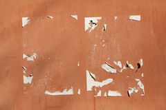 Traces of old announcements on terracotta wall. Background textu Stock Photos