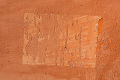 Traces of old announcements on terracotta wall. Background textu Stock Images