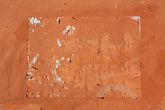 Traces of old announcements on terracotta wall. Background textu Stock Image