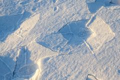 Traces of shoes in the snow close-up. Few traces of men`s shoes in the snow. On the snow there is shadow and cracks. Photographed close-up Royalty Free Stock Images