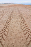 Traces, signs of the tractor on the sand near the sea. Stock Image