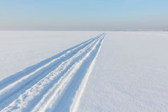Traces from a snowmobile on a snow surface of the river Stock Photo