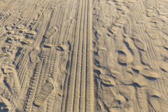 Traces of tires and feet in the beach sand Royalty Free Stock Photography