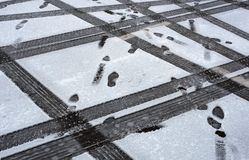 Traces of tires and shoes in the snow. Traces of cars and shoes in the winter season.  Stock Image