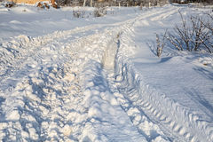 Traces of tractor tires in snow.  Deep furrows. Bright sunlight Royalty Free Stock Photo