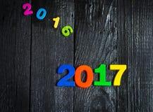 Tracić ważność 2016 Nowy rok 2017, kolorowe postacie na drewnianym tle Zdjęcia Stock