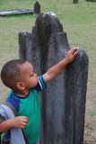 Tracing the Past. A young african american boy puts his hand on a very old gravestone as he learns about the past Stock Images