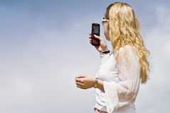 Tracing signal 1. Back side of a young woman wearing a white blouse tracing a signal with her telephone Royalty Free Stock Photo