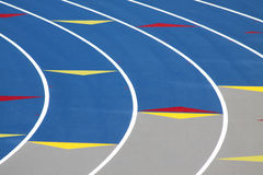 Track. Blue running track with white stripes and yellow and red arrows royalty free stock photo