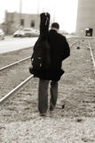 On track. Musician walking on train tracks, motion blur Royalty Free Stock Photography